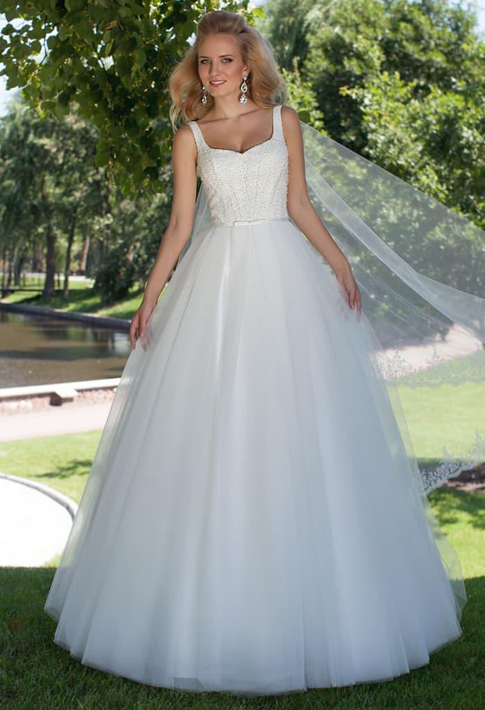 Пышное свадебное платье с открытым лифом и узким глянцевым поясом.