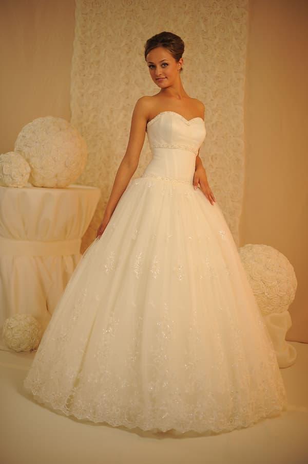 Свадебное платье с лаконичным открытым корсетом и юбкой, декорированной кружевом.