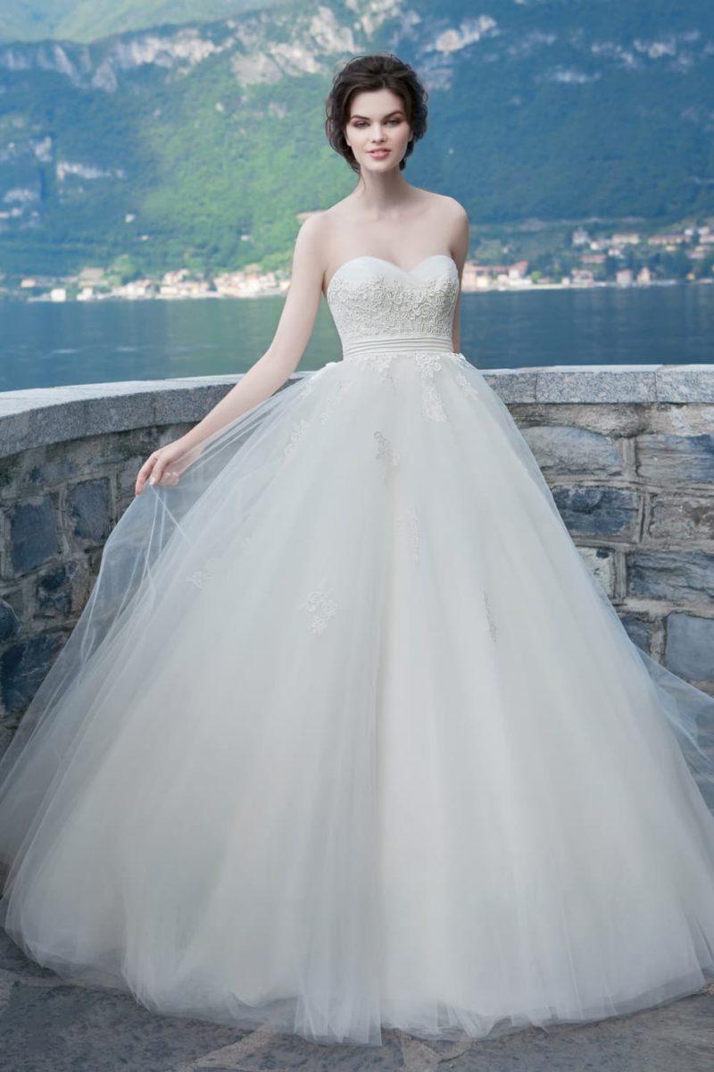 Свадебное платье с открытым лифом в форме сердца и широким поясом, украшенным швами.