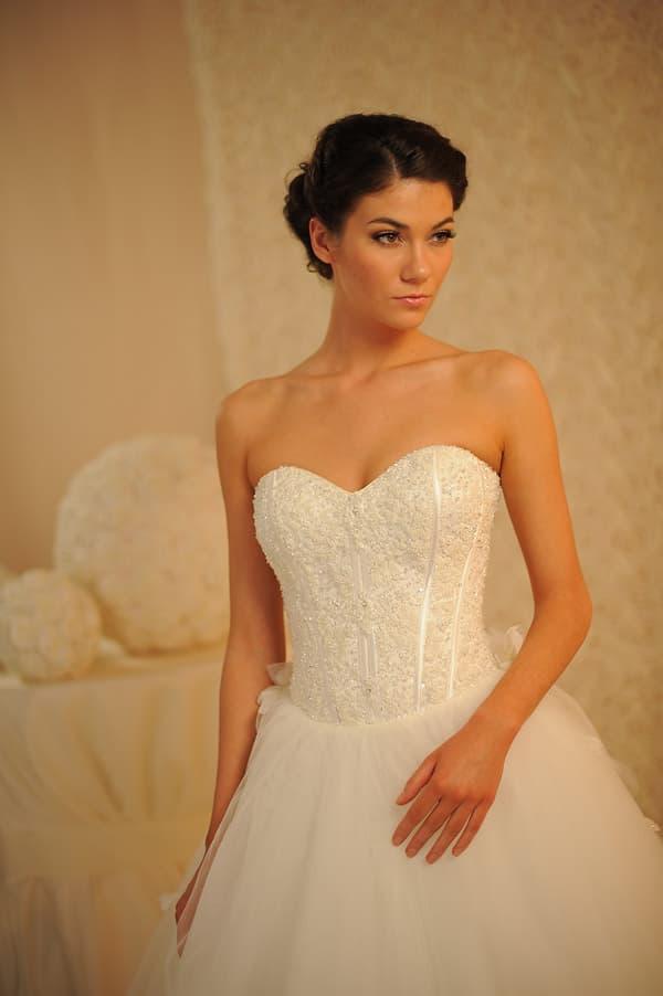 Свадебное платье с многослойной юбкой со шлейфом и корсетом из атласа, украшенным бисером.