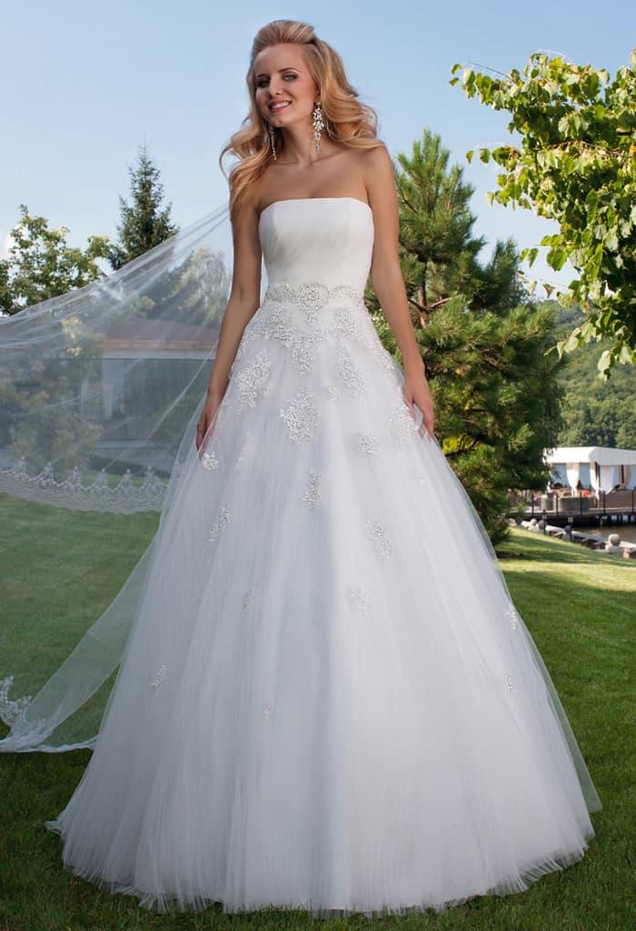 Пышное свадебное платье с открытым лифом прямого кроя и кружевным декором.