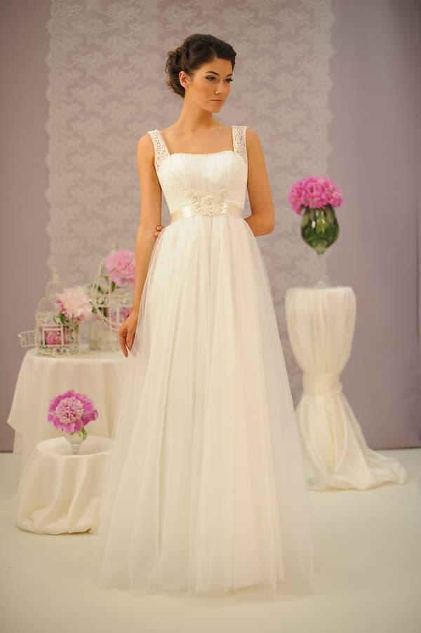 Ампирное свадебное платье с глянцевым поясом и кружевными бретелями на плечах.