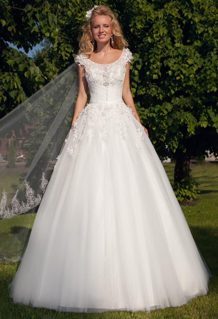 Пышное свадебное платье с глубоким округлым декольте, симметричными бретелями и объемным декором.
