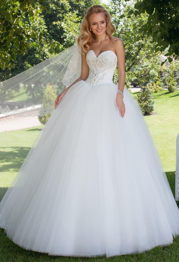 Выразительное свадебное платье с вышивкой на корсете и многослойной юбкой со шлейфом.