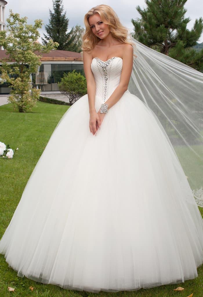 Пышное свадебное платье с лифом в форме сердца, украшенным полосой бисера спереди.
