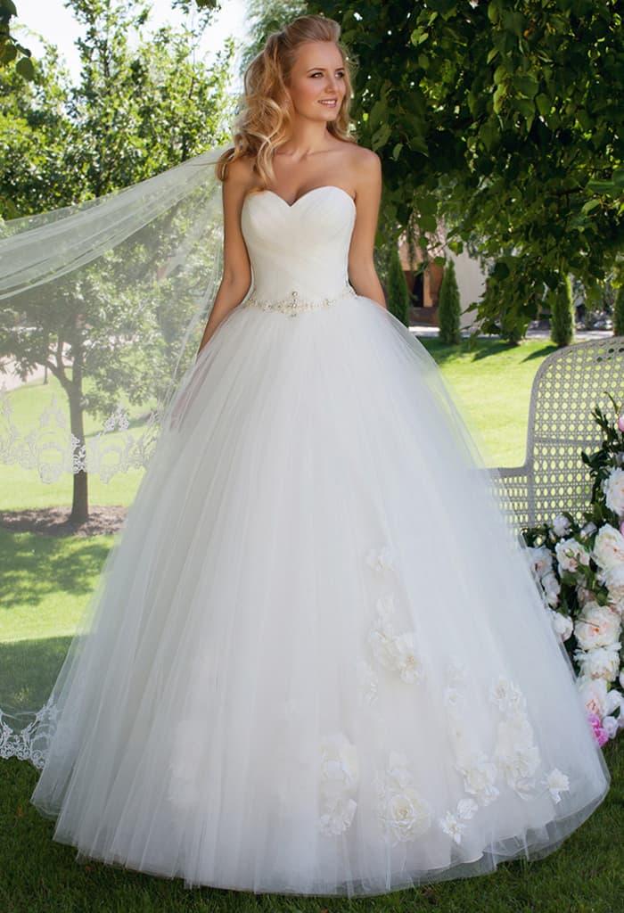 Изысканное свадебное платье пышного кроя с лифом в форме сердечка и сияющим поясом.