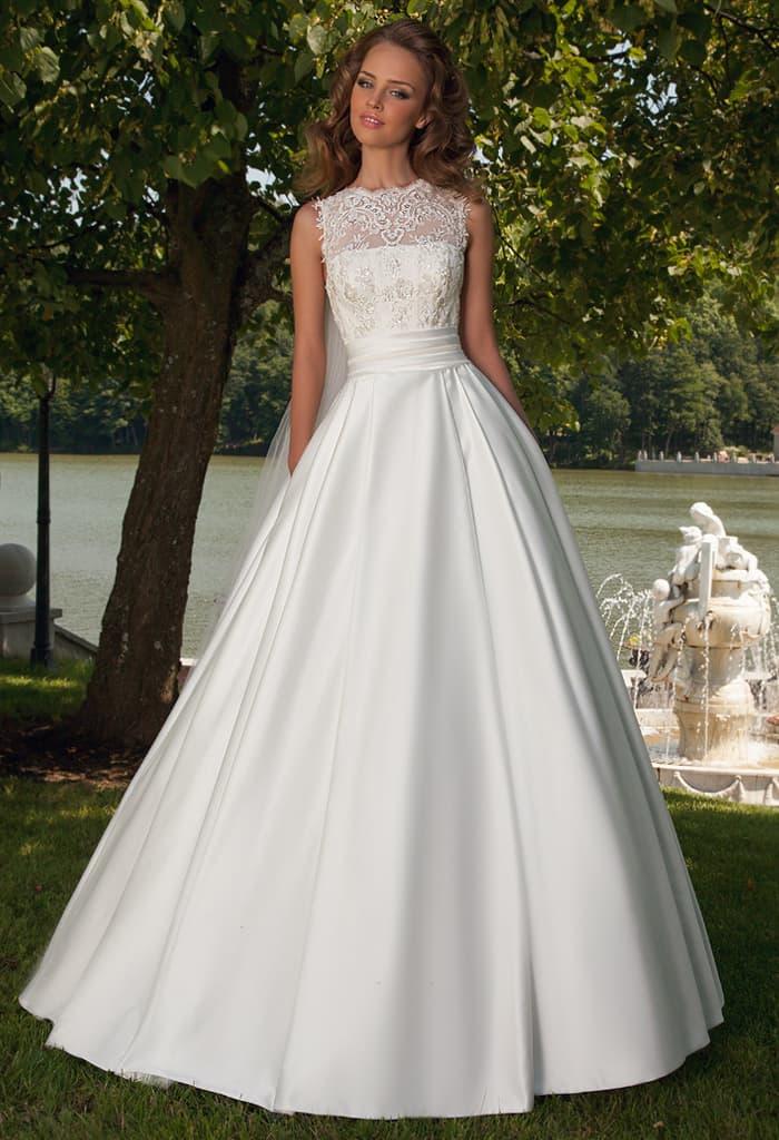 Выразительное свадебное платье из плотного атласа, дополненного сверху кружевом.