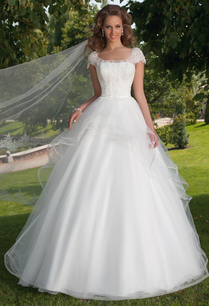 Элегантное свадебное платье с многослойной юбкой и короткими рукавами.