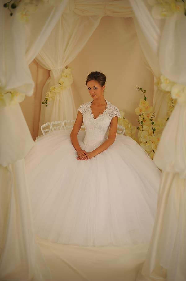 Пышное свадебное платье с небольшим вырезом, обрамленным кружевной тканью.