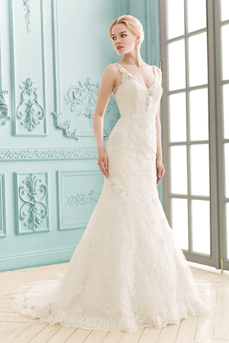 Свадебное платье с кружевными бретелями, создающими V-образным вырез, и облегающим силуэтом.