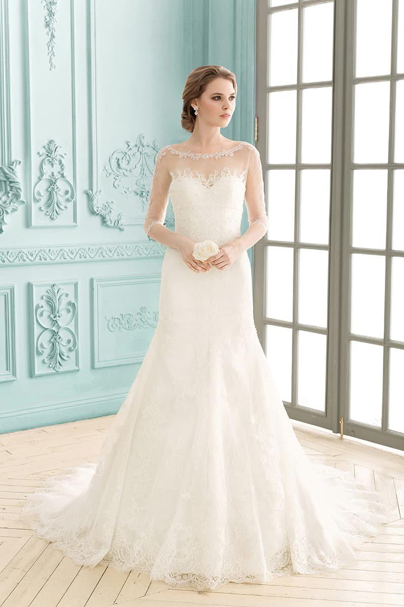 Закрытое свадебное платье с округлым декольте и длинными прозрачными рукавами.