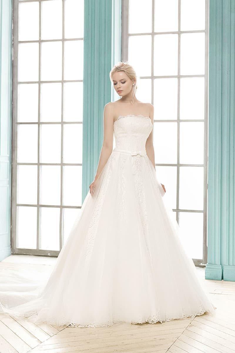 Свадебное платье пышного кроя с открытым лифом, декорированным кружевом, и узким поясом.