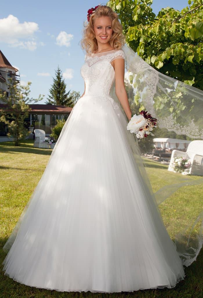 Великолепное свадебное платье с округлым вырезом декольте и торжественной многослойной юбкой.