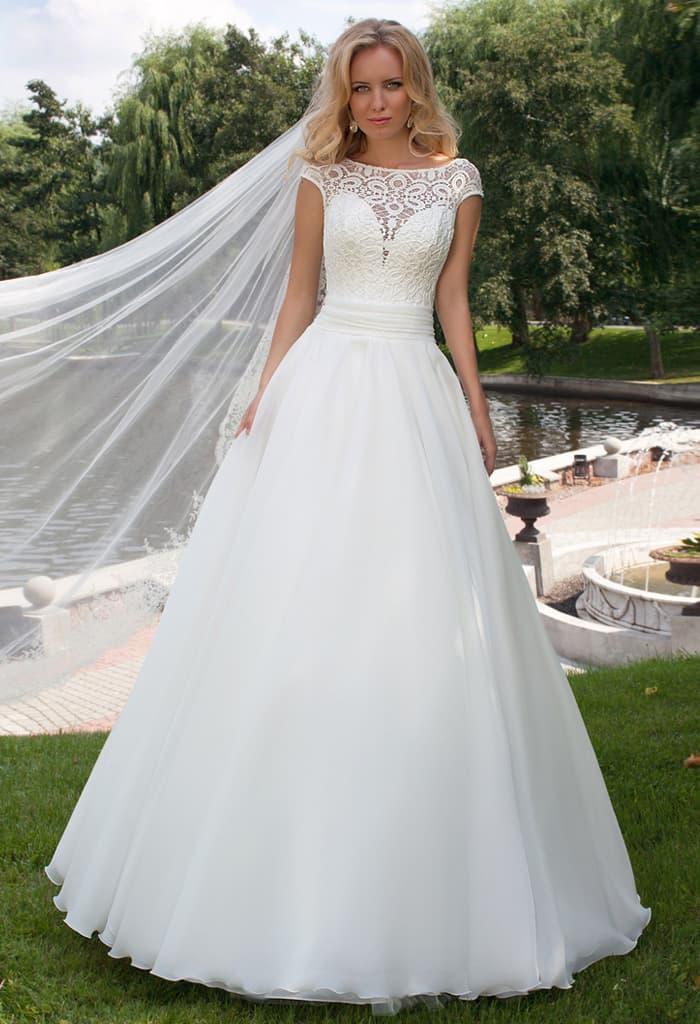 Пышное свадебное платье с ажурным лифом и широким поясом на талии.