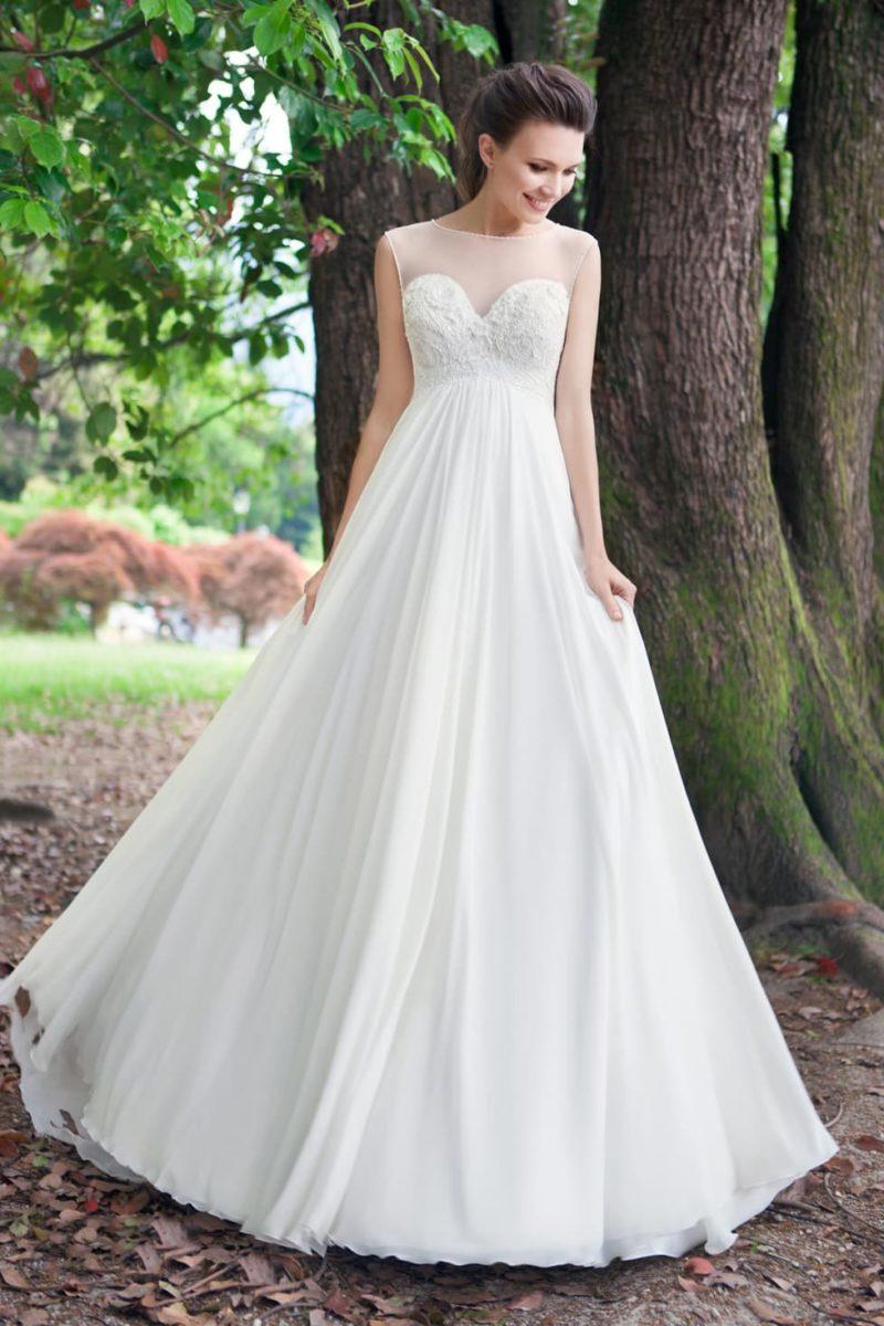 Стильное свадебное платье с завышенной линией талии и полупрозрачным декором декольте.