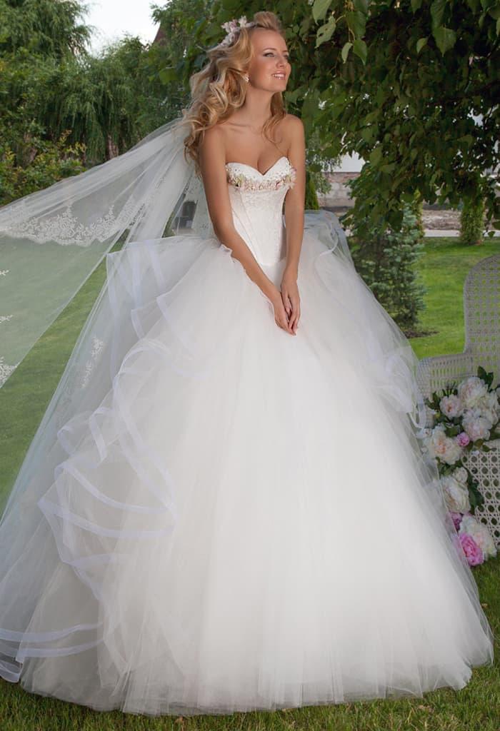 Открытое свадебное платье с пышными оборками по бокам подола и бисером на лифе.