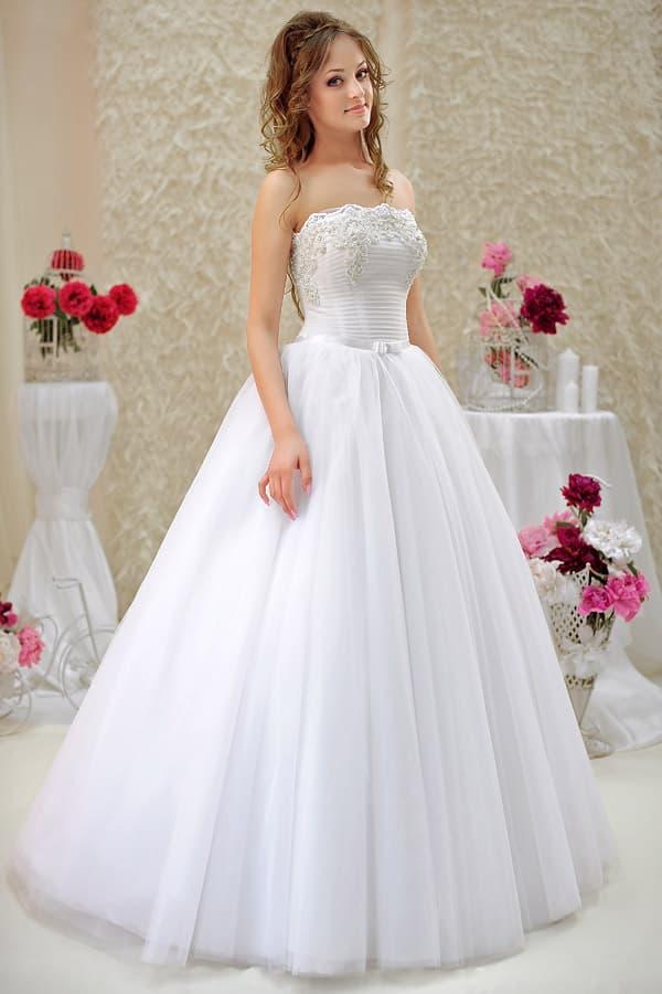 Пышное свадебное платье с бантом на талии и кружевным фигурным декольте.