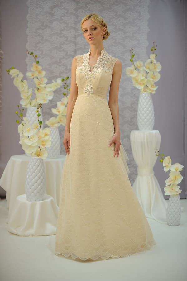 Бежевое свадебное платье облегающего кроя с кружевным воротником-стойкой.