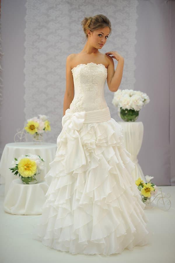 Свадебное платье с фигурным открытым лифом и юбкой, покрытой оборками.