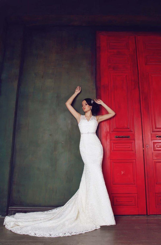 Свадебное платье с V-образным декольте, узким бисерным поясом и юбкой «рыбка» со шлейфом.