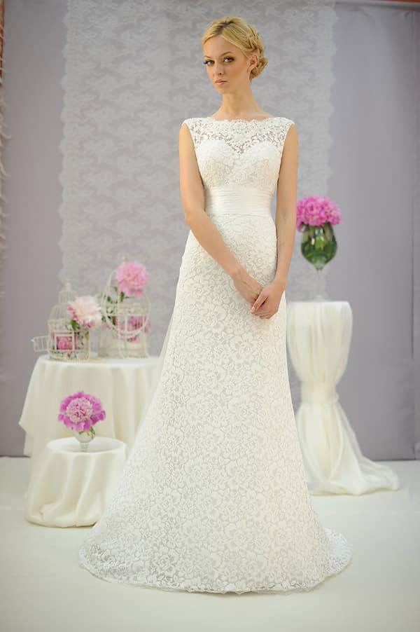 Скромное свадебное платье с широким поясом, полностью покрытое кружевом.