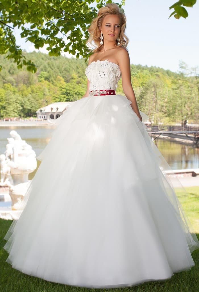 Торжественное свадебное платье пышного кроя с объемным декором корсета и алым поясом.