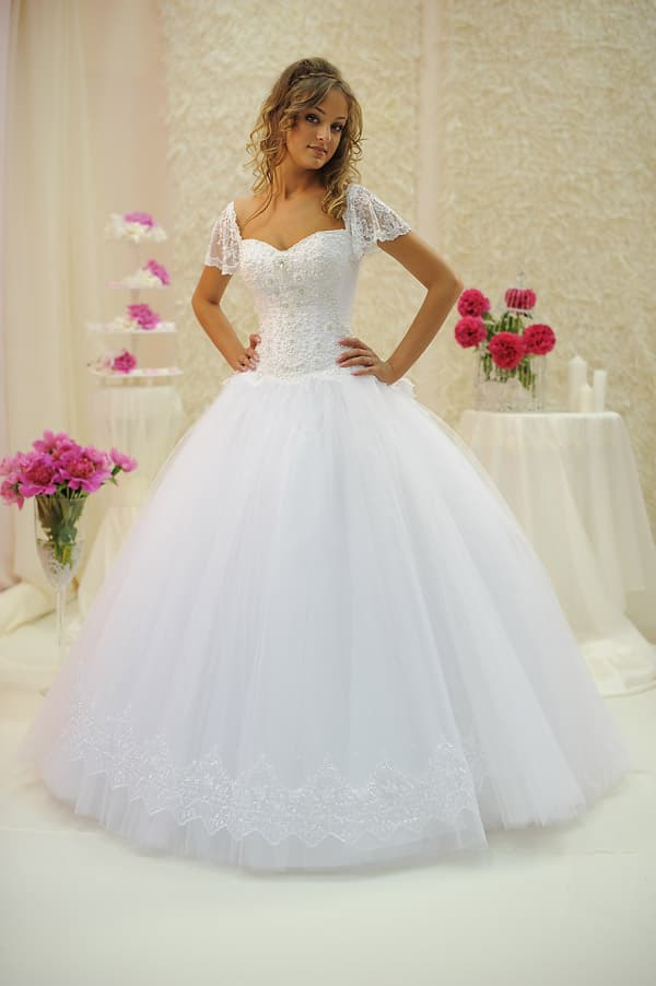 Свадебное платье с украшенной кружевом пышной юбкой и широкими рукавами.