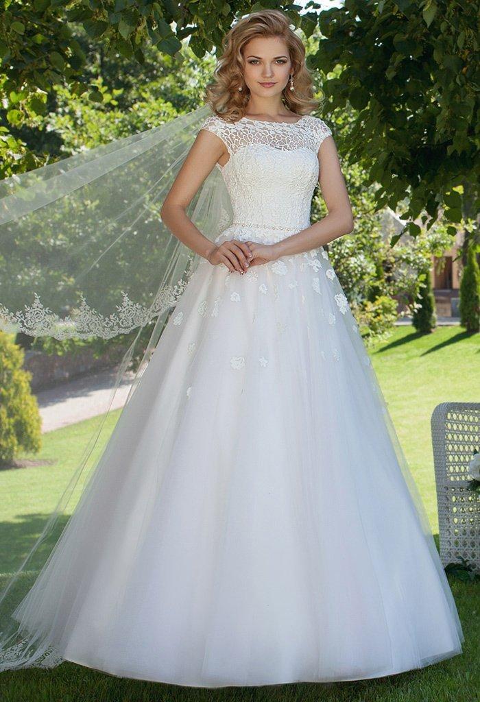 Роскошное свадебное платье с кружевным верхом и многослойной юбкой.