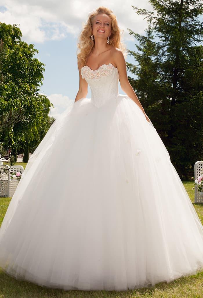 Пышное свадебное платье с открытым лифом, нежно украшенным объемными бутонами.