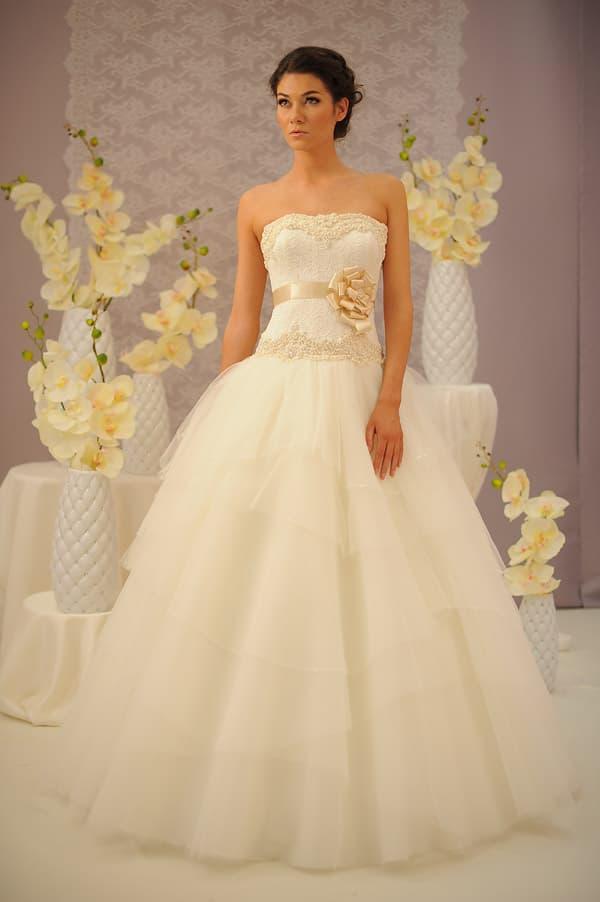 Бежевое свадебное платье пышного кроя с золотым атласным поясом с бутоном сбоку.