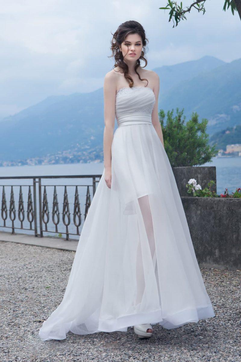Лаконичное свадебное платье с драпировками и полупрозрачной верхней юбкой.