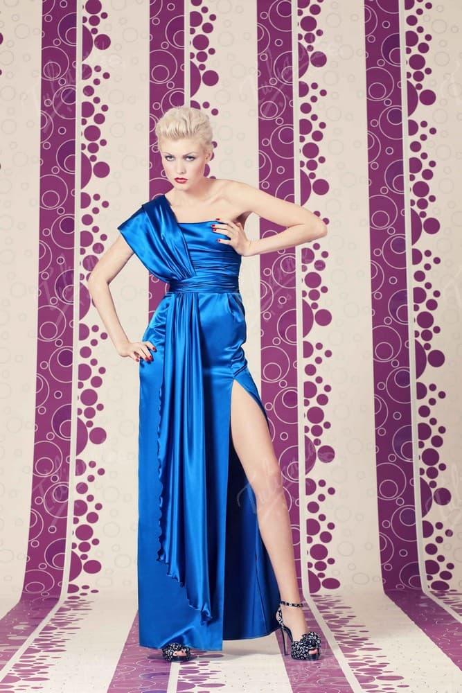 Глянцевое вечернее платье синего цвета с разрезом сбоку по подолу.