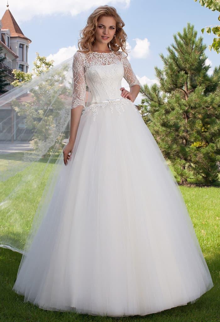Закрытое свадебное платье пышного кроя с кружевным рукавом и вырезом сзади.