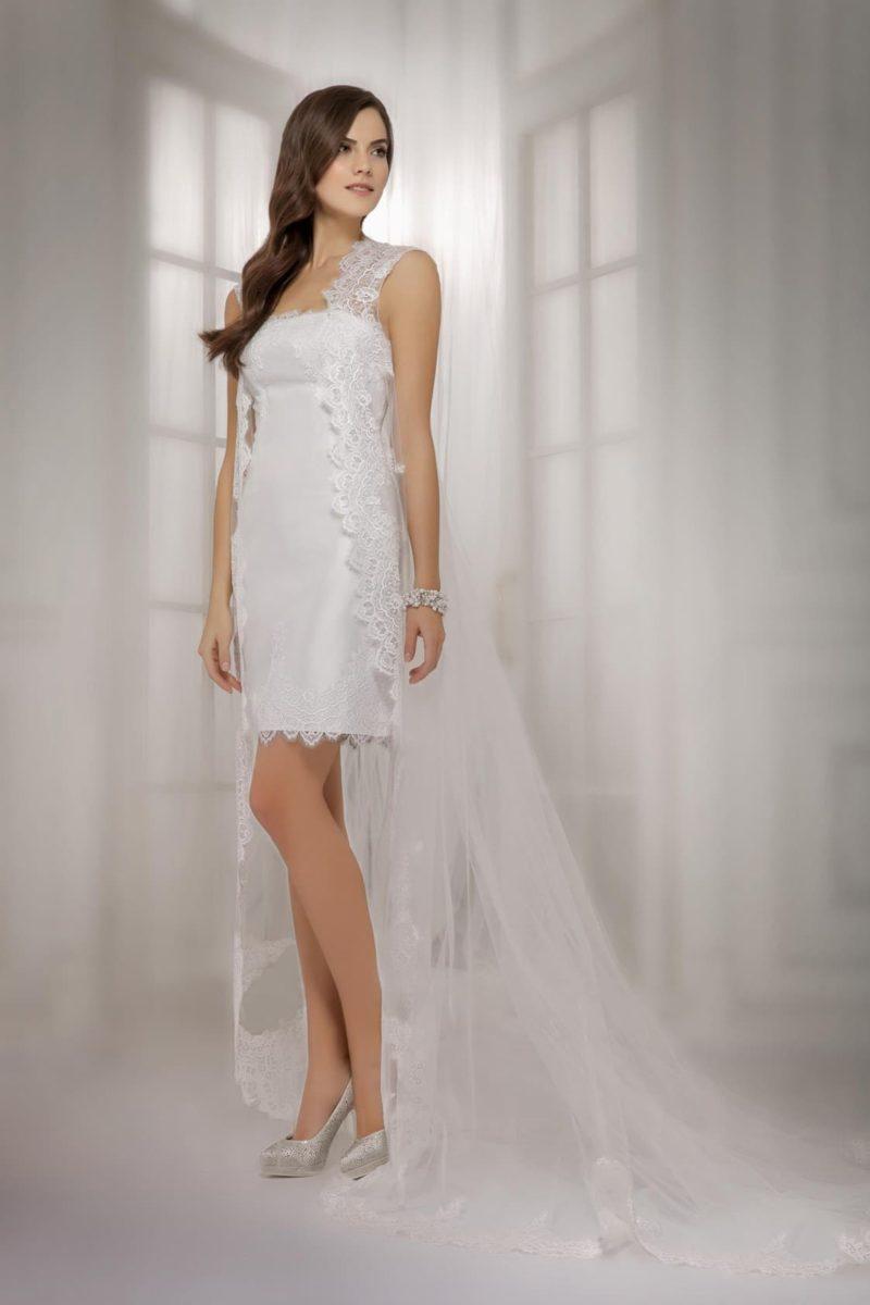 Короткое свадебное платье-футляр из атласной ткани с длинной кружевной накидкой.