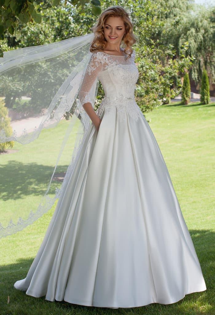 Атласное свадебное платье А-кроя с элегантным полупрозрачным рукавом.