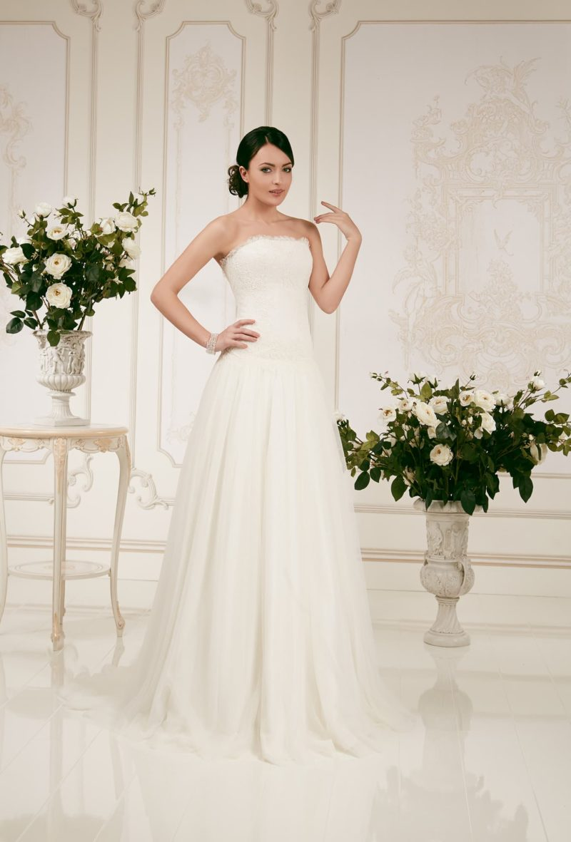 Утонченное свадебное платье с лаконичным открытым лифом прямого кроя, украшенным кружевом.