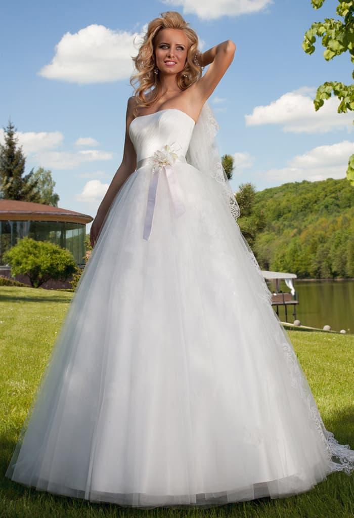 Открытое свадебное платье пышного кроя с поясом, украшенным сбоку бутоном.