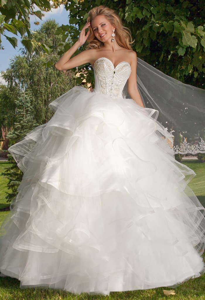 Великолепное свадебное платье с соблазнительным корсетом и пышными оборками по юбке.