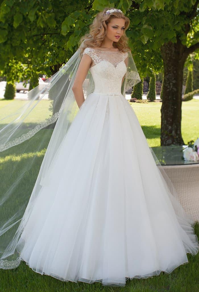 Пышное свадебное платье с округлым вырезом, оформленным полупрозрачной тканью.