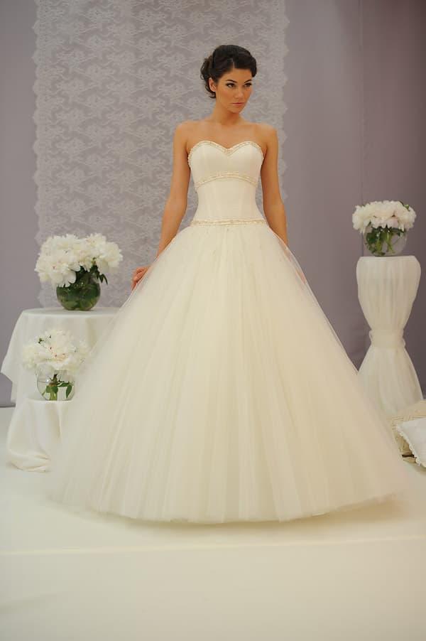 свадебное платье А-силуэта оттенка слоновой кости, декорированное тесьмой по корсету.