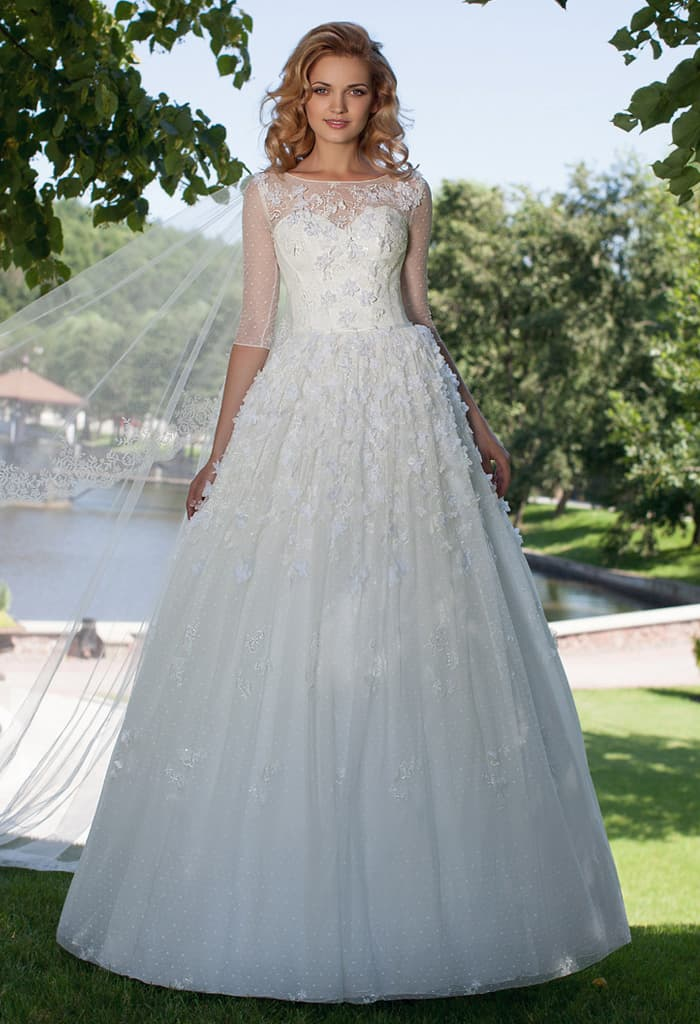 Пышное свадебное платье с объемной отделкой и рукавом длиной три четверти.