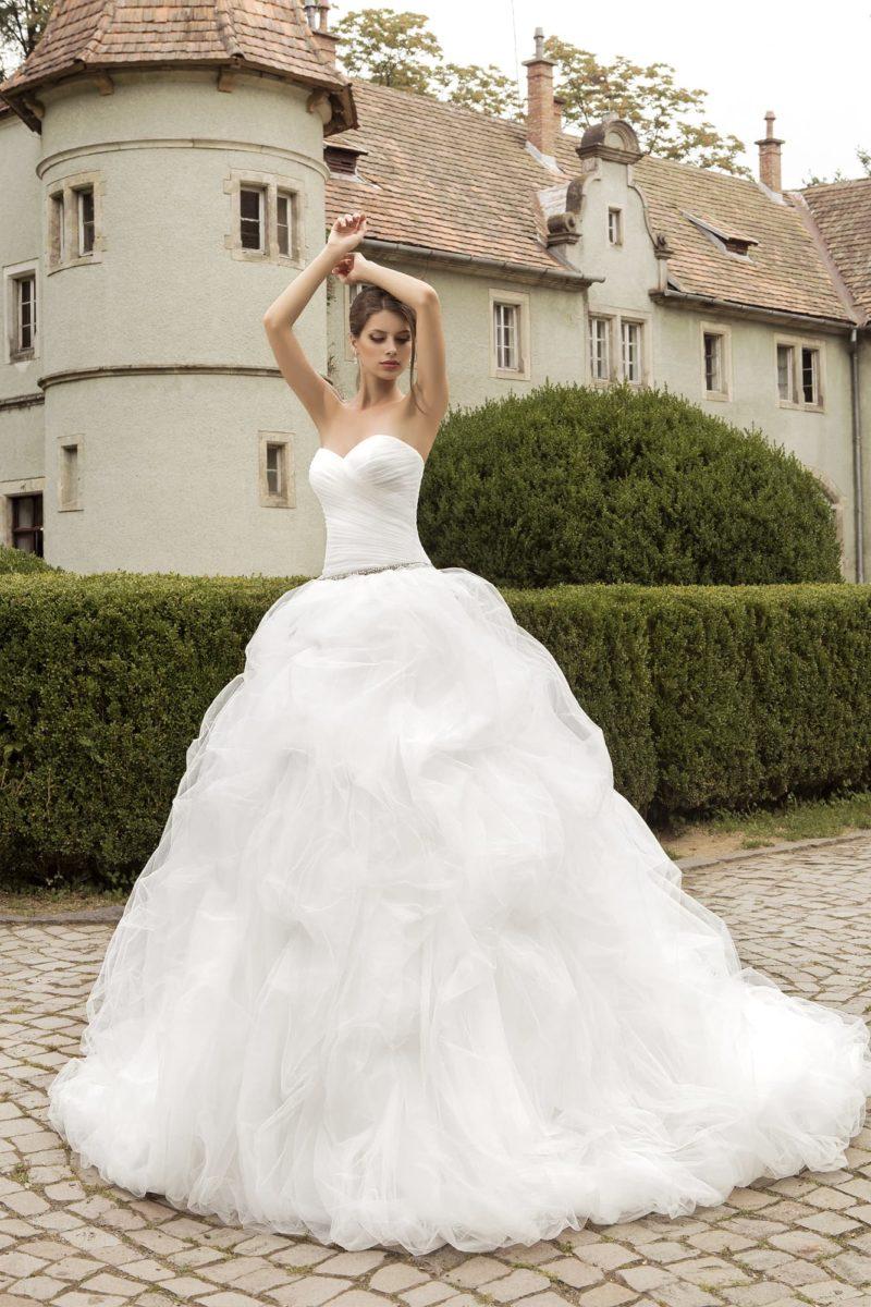 Романтичное свадебное платье с драпировками по корсету и пышной отделкой подола.