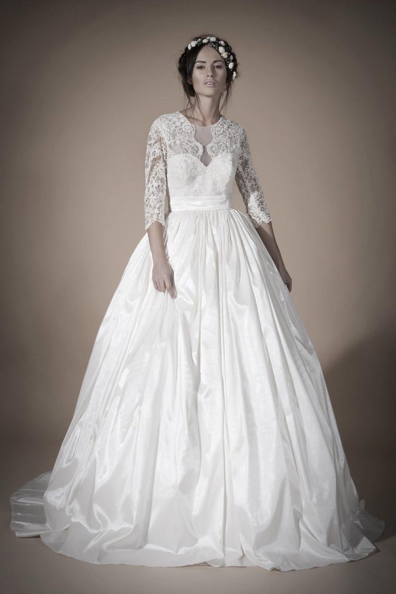 Свадебное платье с пышной юбкой из фактурной ткани и длинными кружевными рукавами.