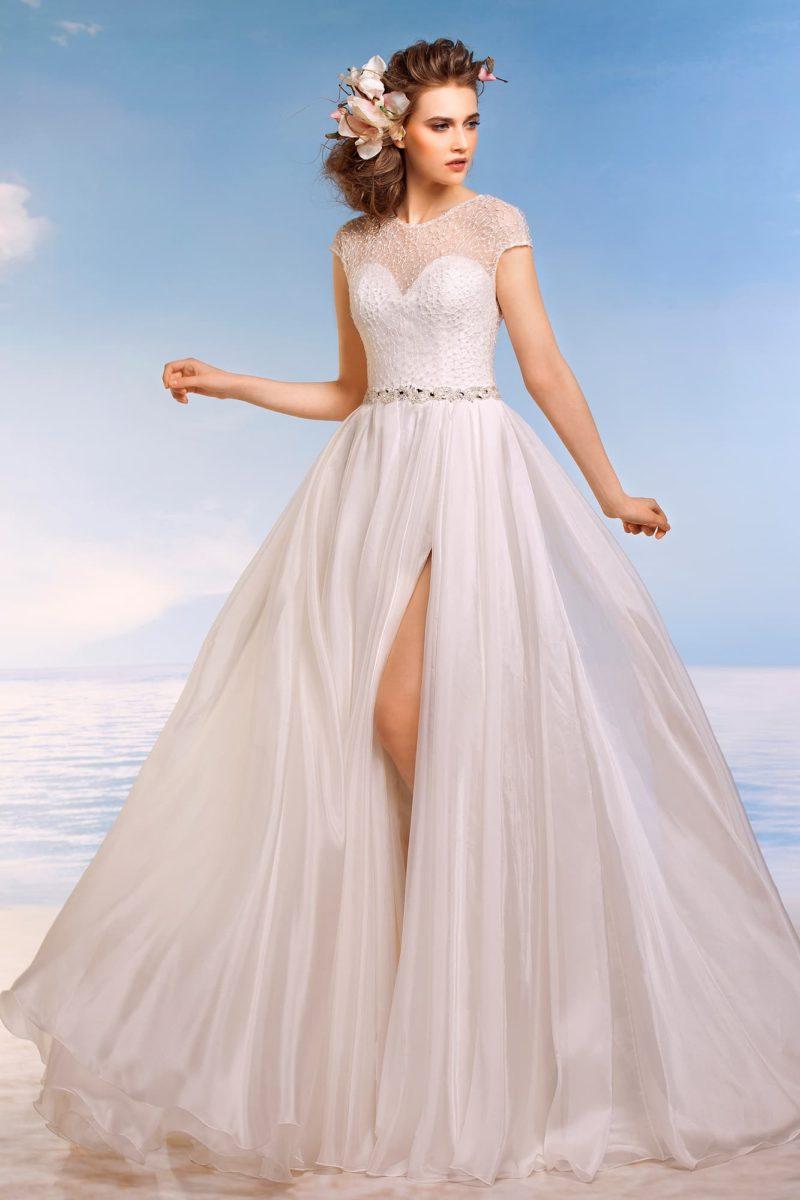 Пышное свадебное платье с разрезом на юбке и фактурным декором поверх открытого корсета.