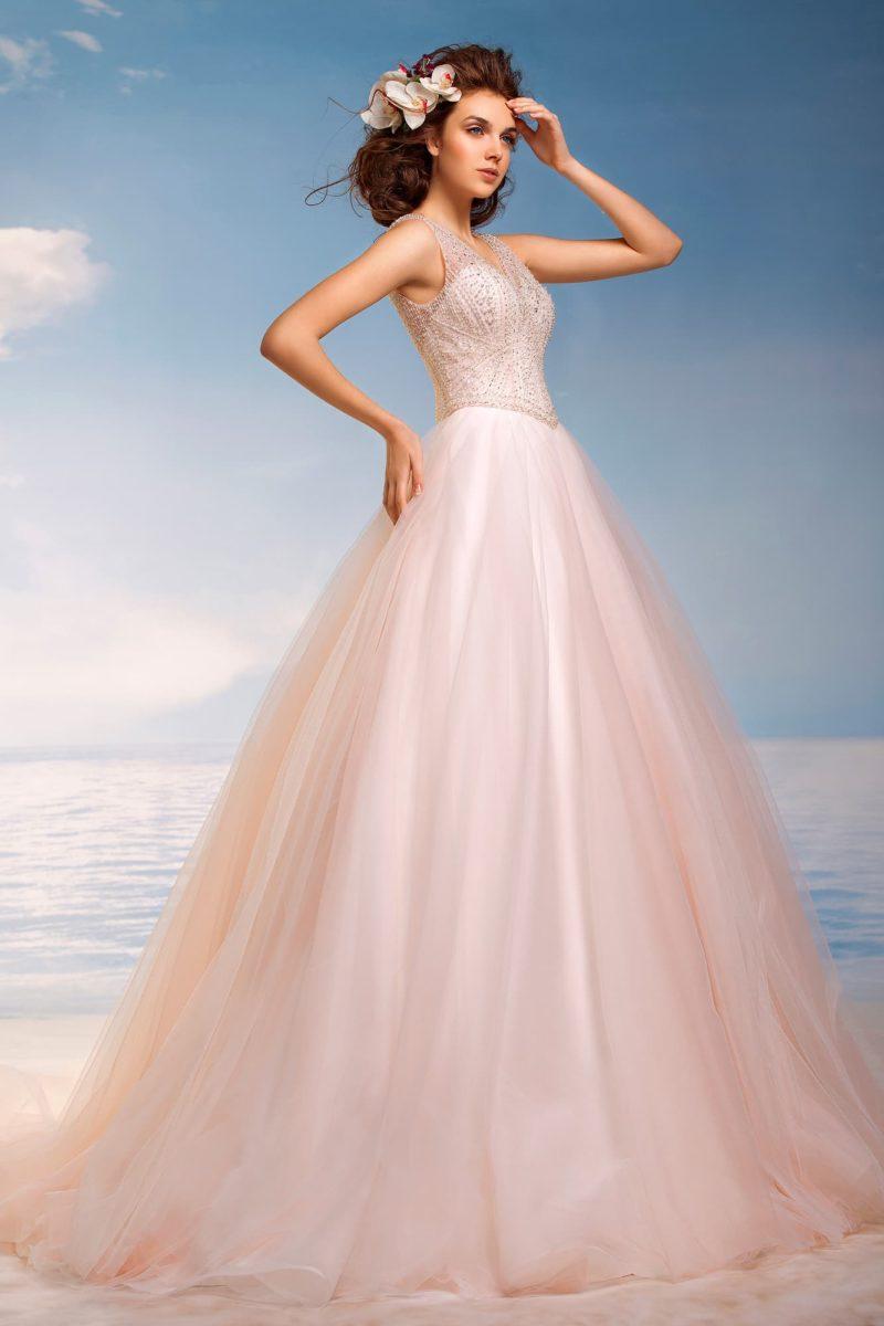 Кремовое свадебное платье пышного кроя с V-образным декольте и бисерной отделкой по верху.