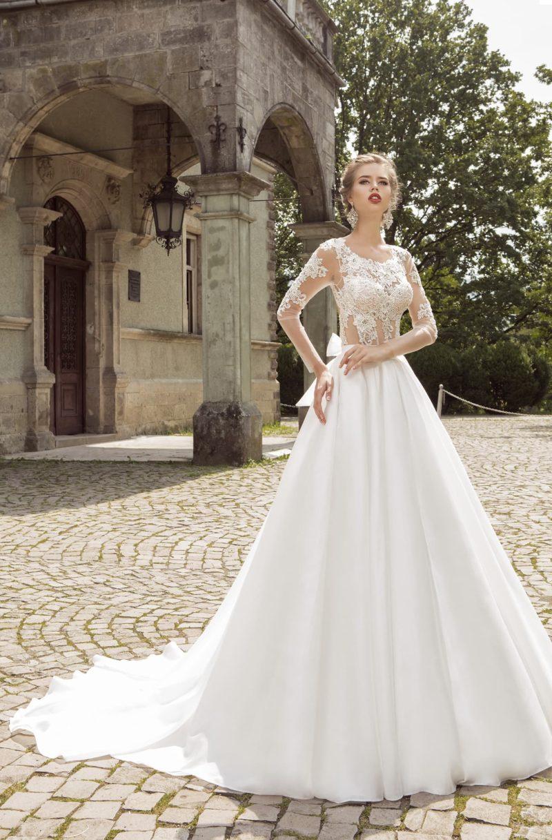 Свадебное платье с полупрозрачным кружевным корсетом, открытой спиной и пышным бантом сзади.