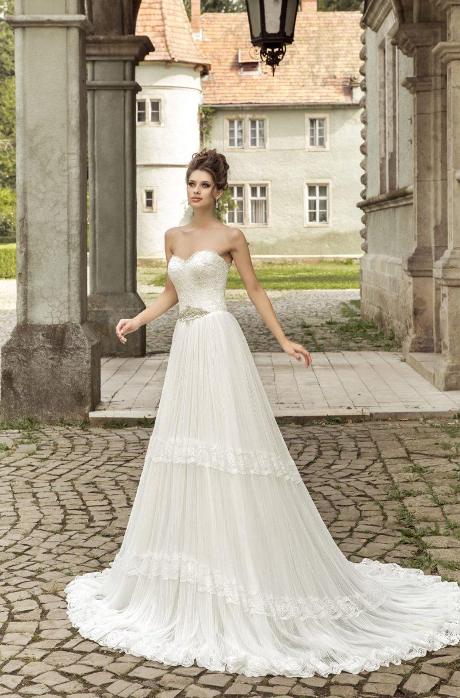 Свадебное платье с элегантным открытым корсетом и многоярусной юбкой со шлейфом.