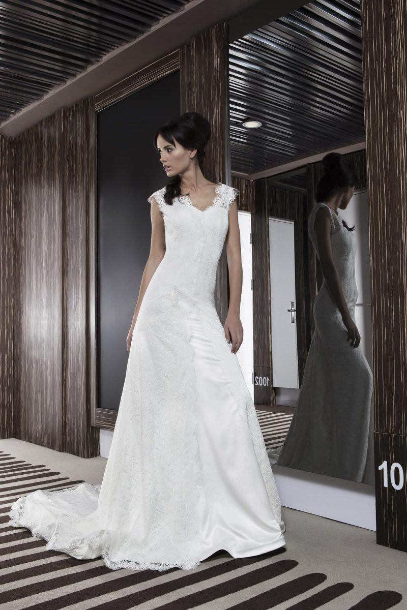 Прямое свадебное платье с V-образным декольте и длинным кружевным шлейфом сзади.