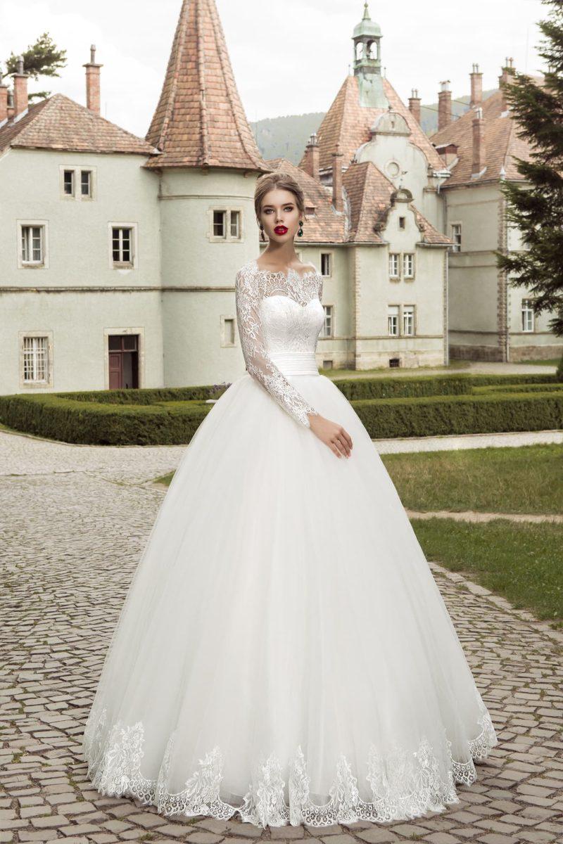 Пышное свадебное платье с широким атласным поясом и кружевной отделкой закрытого лифа.