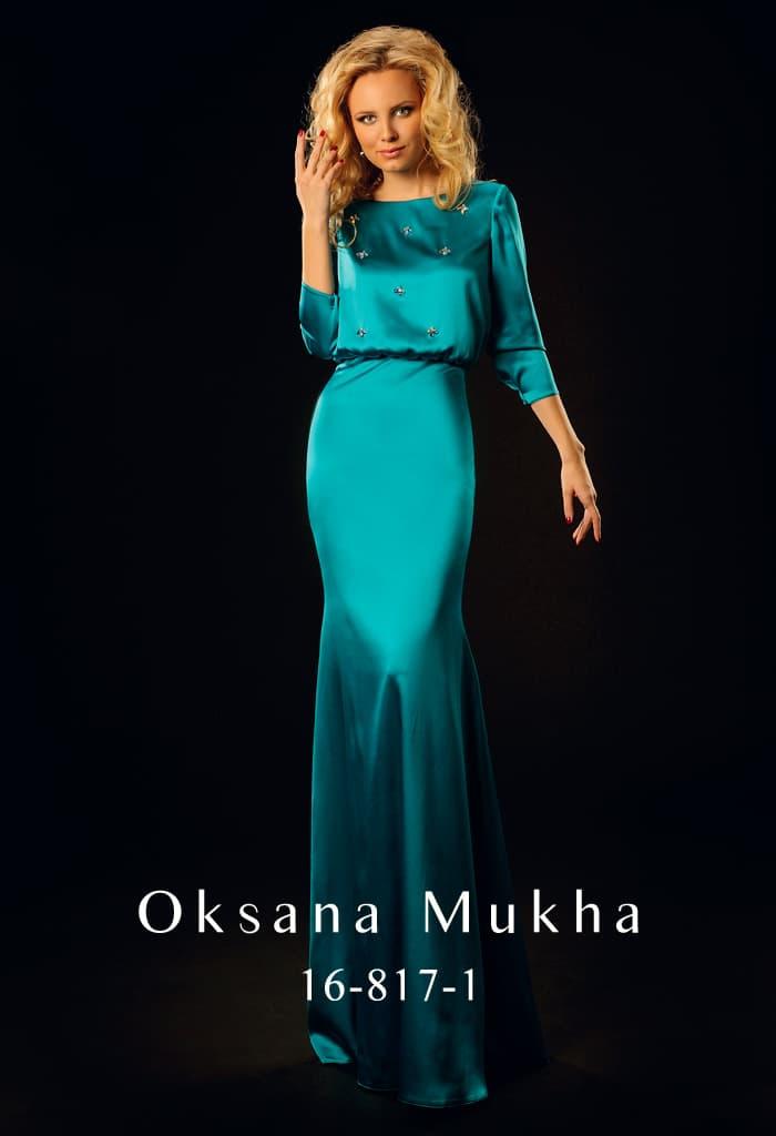 Атласное вечернее платье изумрудного цвета с округлым декольте и длинным рукавом.
